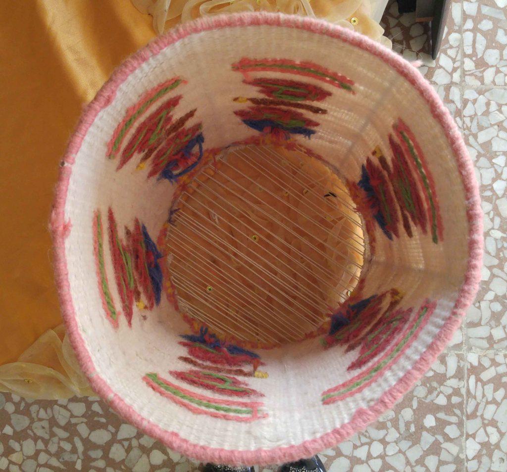 نمای داخل سطل آشغالی که چله کشی کرده و بافه گلیم روش انجام شده.